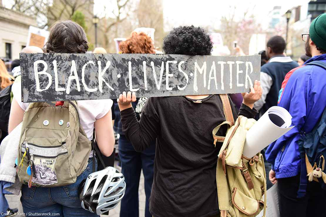 "Protestors hold ""Black Lives Matter"" sign over their shoulders at a rally in Union Square before marching to Lower Manhattan."