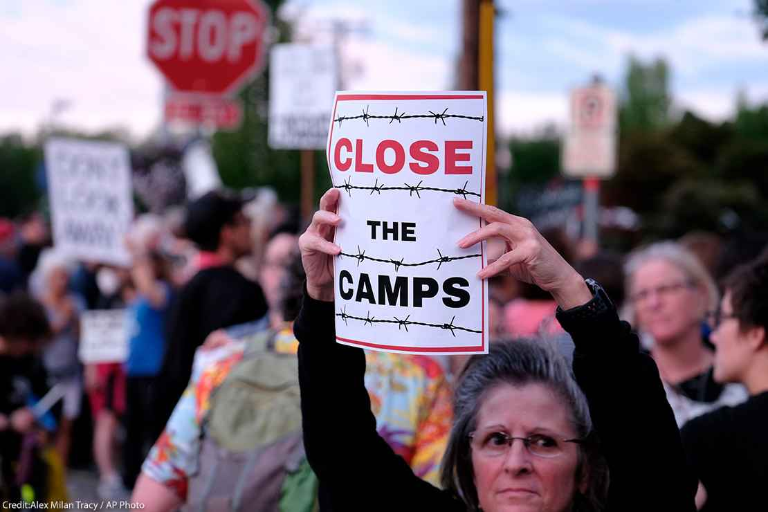 """Woman holds sign that reads """"Close the Camps"""" outside of the Immigration and Customs Enforcement (ICE) office in Portland"""