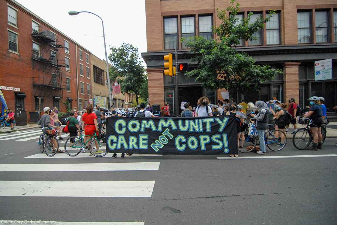 Protesters hold a banner calling for investment in communities, not the police