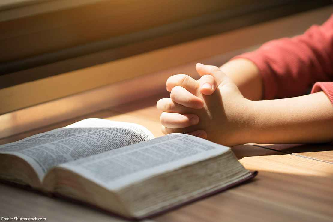 A boy whose hands are folded in prayer in front of a Bible on a desk.