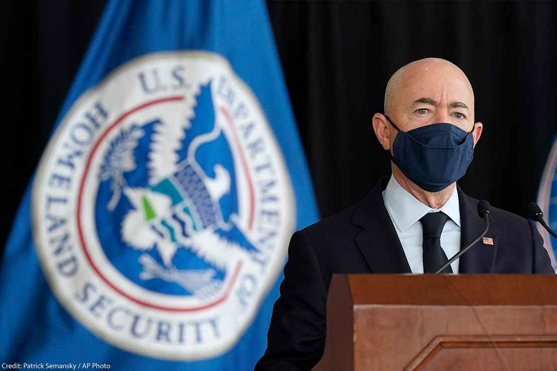 Secretary of Homeland Security Alejandro Mayorkas speaks during news conference with a U.S. Homeland Security flag behind him.