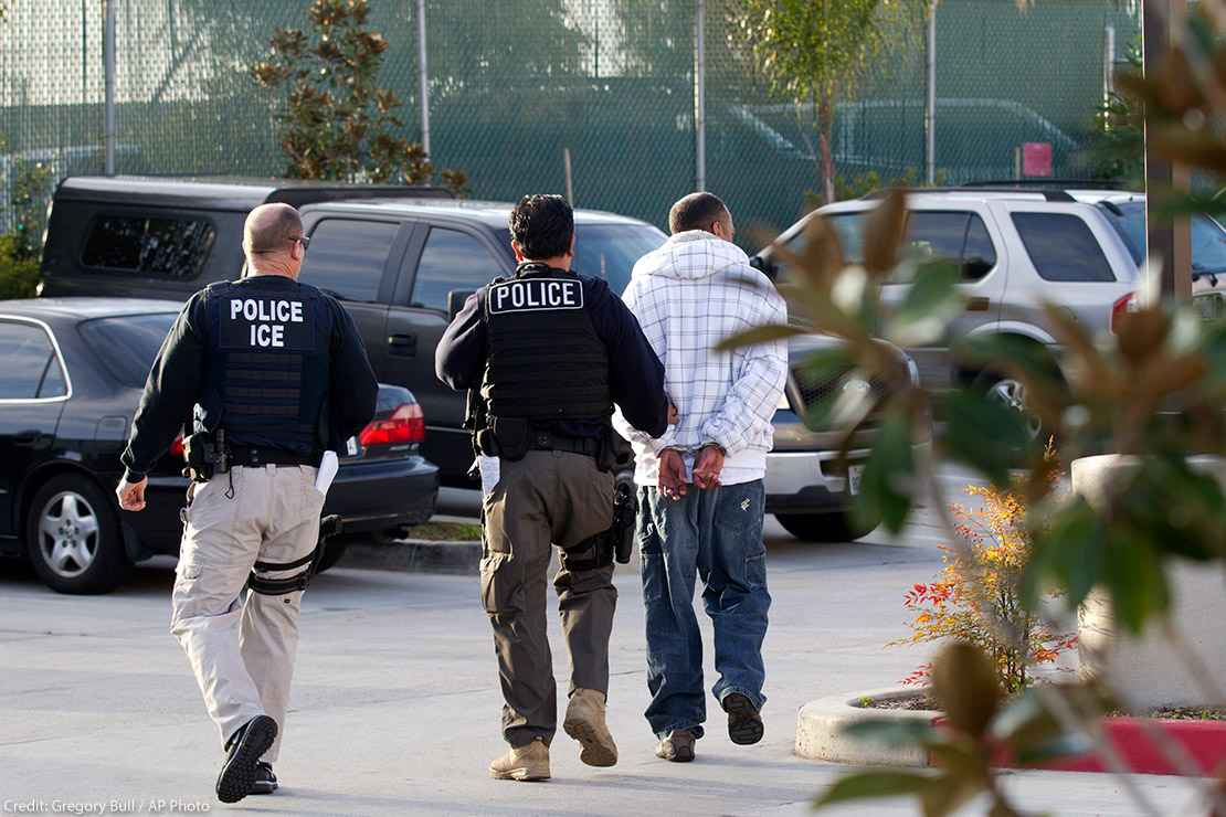 Two Immigration and Customs Enforcement (ICE) agents take a person into custody