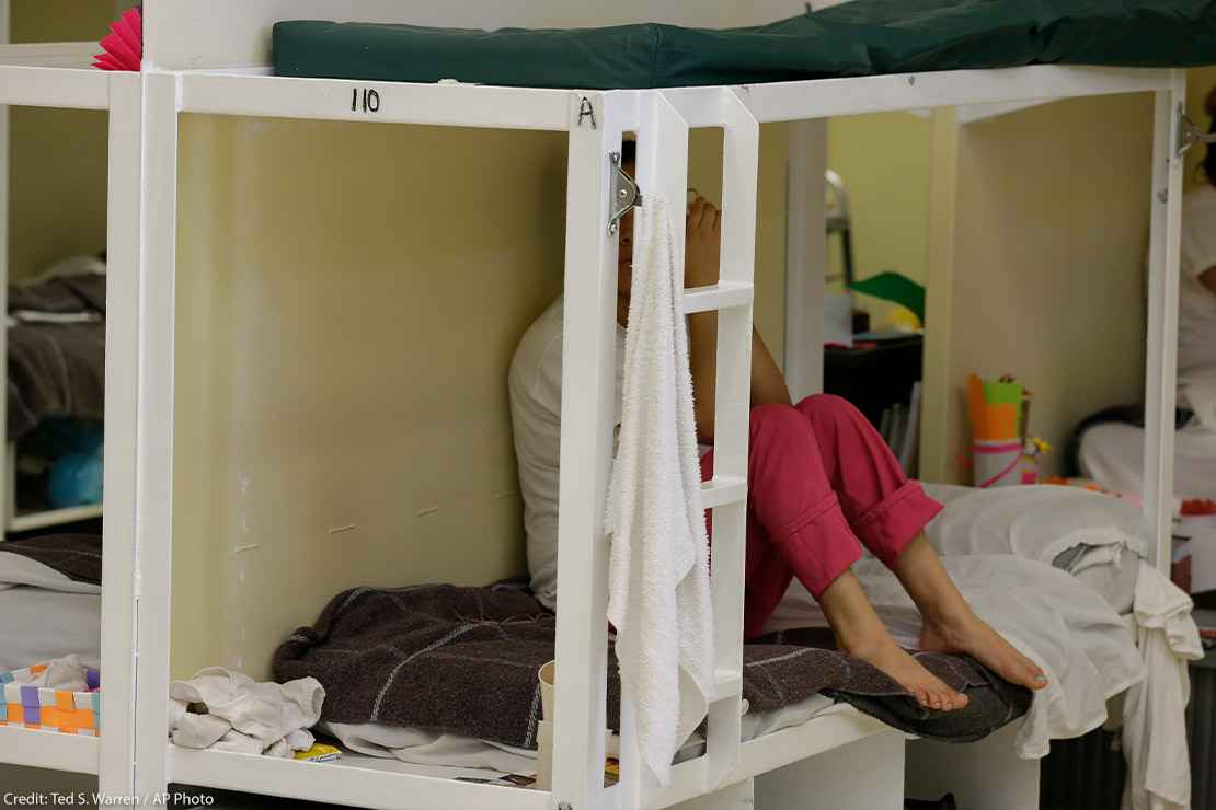 A detainee sits on a bunk in a women's area at an immigration detention center.