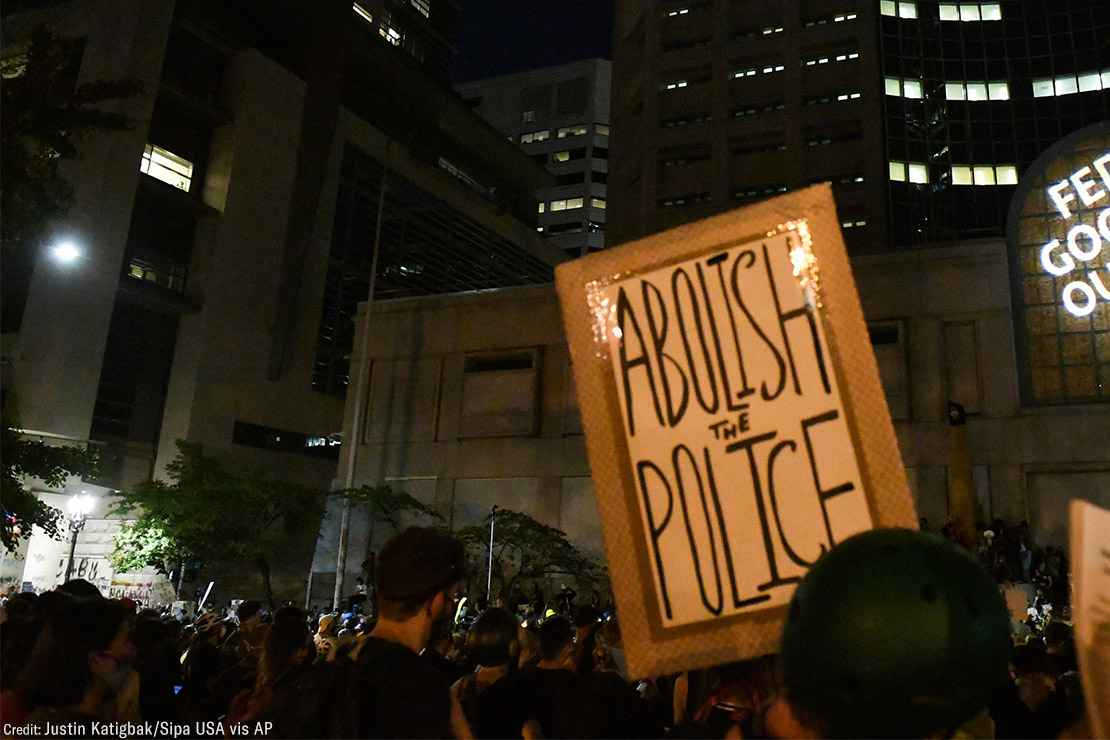 """A group of protesters with one holding a sign with the text, """"Abolish the Police."""""""