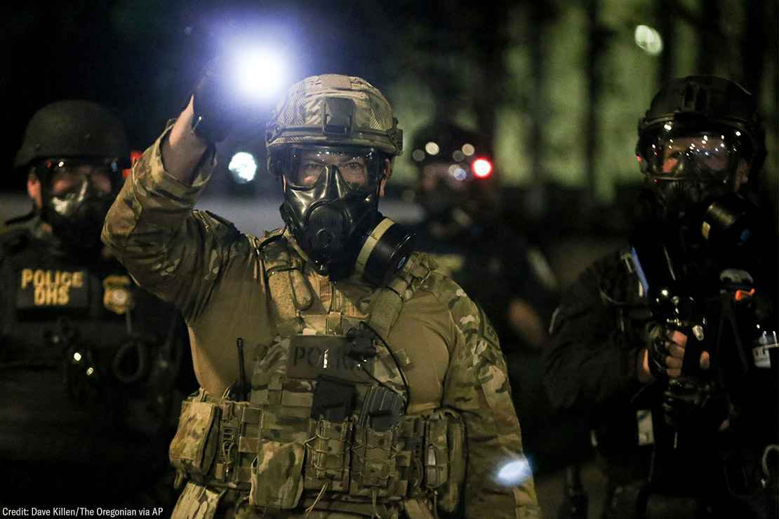 A group of militarized federal agents with an agent in the center shining a bright flashlight toward the viewer.