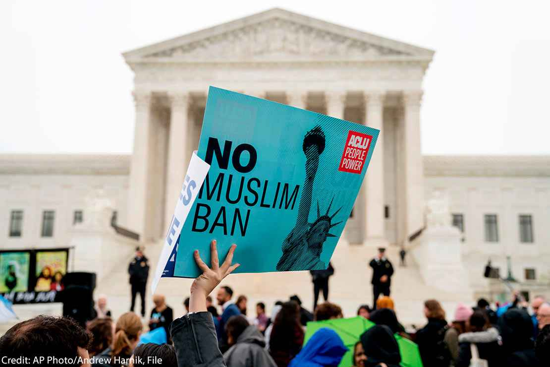 """In this April 25, 2018 file photo, a person holds up a sign that reads """"No Muslim Ban"""" during an anti-Muslim ban rally in front of the Supreme Court building in Washington, DC."""