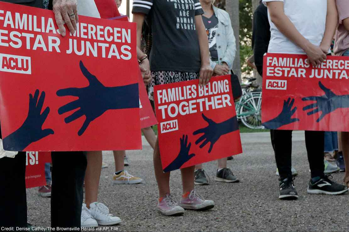 """People hold signs that read """"families belong together"""" in both English and Spanish during a vigil."""