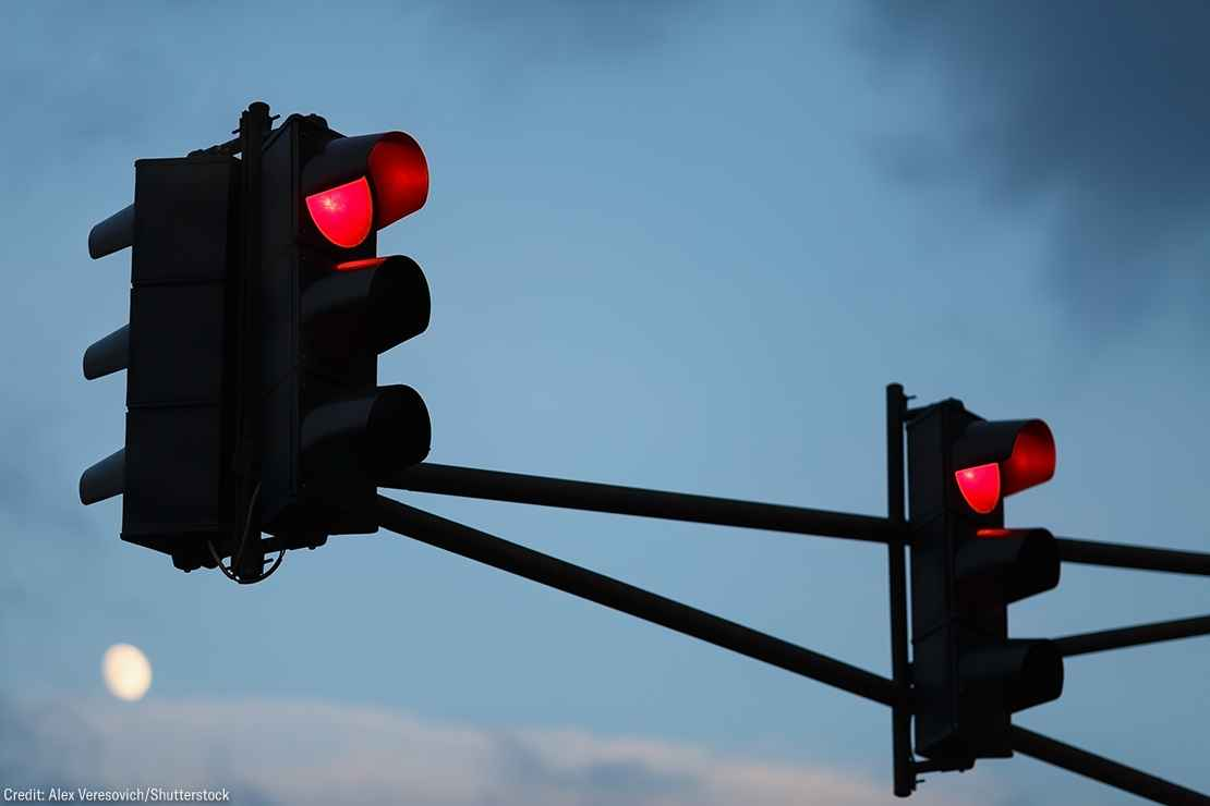 Traffic light with red light against the evening sky. Shallow depth of field.