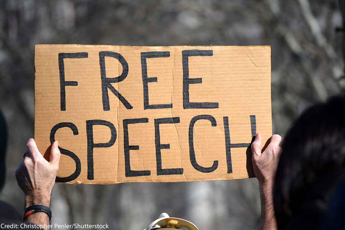 A sign reading FREE SPEECH is held aloft by person protesting immigration laws banning some Muslims at Battery Park in Manhattan in 2017 in New York City