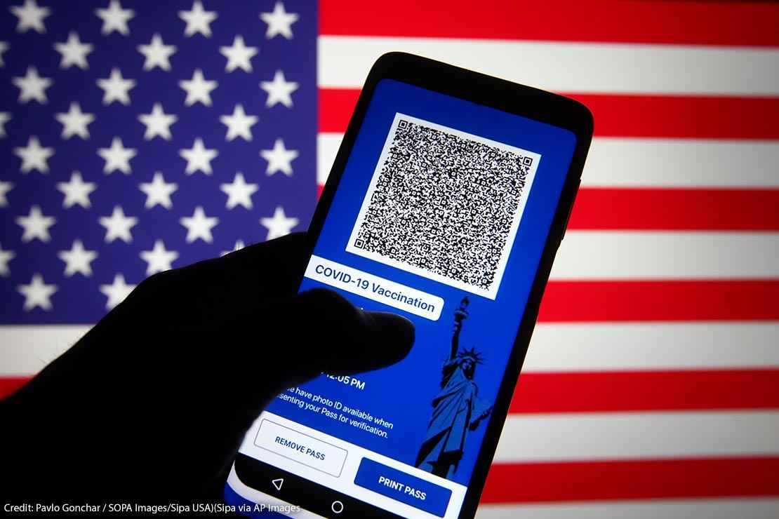 In this photo illustration, Excelsior Pass app which provides digital proof of COVID-19 vaccination or negative test results seen displayed on a smartphone screen in front of the US flag.
